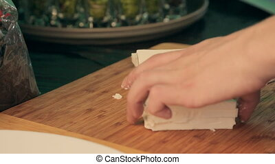 The process of cutting the feta cheese into cubes by chef -...