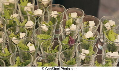 Cook adds cubes of feta cheese in containers with lettuce on...