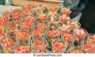Portions with salad of vegetables and fish on a tray in the catering