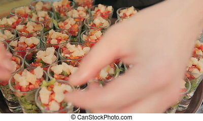 Waiter puts the pieces of fish in portions with vegetable salad on catering