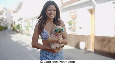 Smiling young woman cuddling a small dog - Smiling...