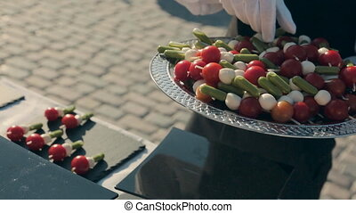 Waiter puts canape with cherry tomatoes and cheese on a...