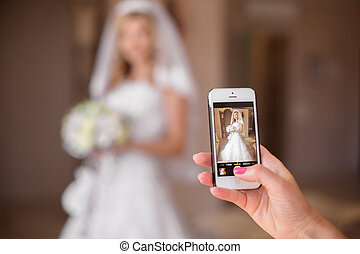 Taking photo of beautiful bride on mobile smart phone....