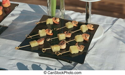 Canape of shrimp and pineapple on skewer at catering -...