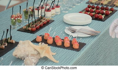 Waiter puts a tray with sushi on the table with snacks at a banquet