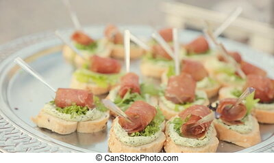 Delicious sandwiches with cream cheese, leaf of lettuce and a piece of ham on catering