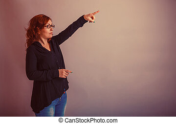 European -looking woman of 30 years is pointing in the...