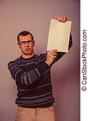 European-looking man of 30 years holding a blank sheet, resentment