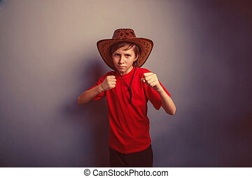 Boy, teenager, twelve years in red t-shirt with cowboy hat...