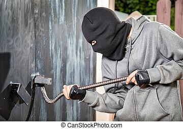 Burglary - a burglar breaking open of a padlock metal door