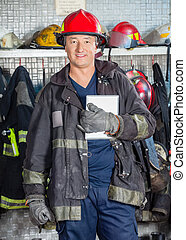 Smiling Worker Holding Digital Tablet At Fire Station -...