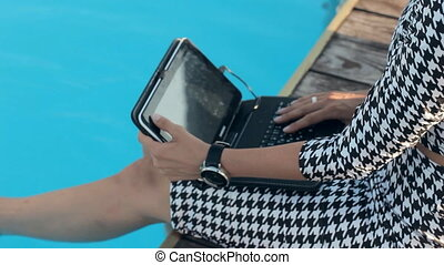 Business woman sitting on the edge of the pool with a laptop