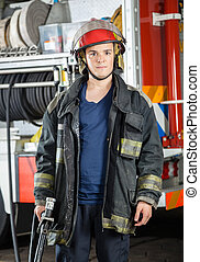 Confident Firefighter Holding Hose At Fire Station -...