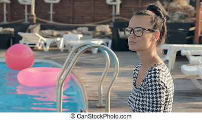 Business woman sitting at a wooden pier near the pool with laptop