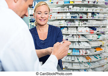 Pharmacist Explaining Product Details To Customer