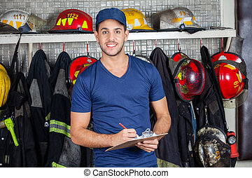 Confident Worker Holding Clipboard At Fire Station -...