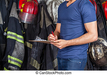 Fireman Writing On Clipboard - Midsection of fireman writing...