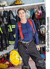 Firewoman Holding Helmet At Fire Station - Portrait of...