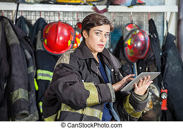 Confident Firewoman Using Digital Tablet At Fire Station -...