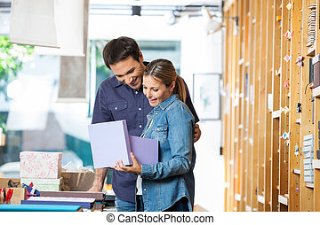 Woman Holding Gift Box While Standing With Man In Store