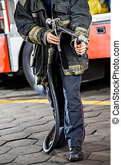 Firefighter Holding Water Hose At Fire Station - Low section...