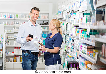 Customer Holding Mobile Phone While Chemist Showing Him...