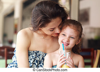 Happy mother looking and hugging her daughter who drinking...