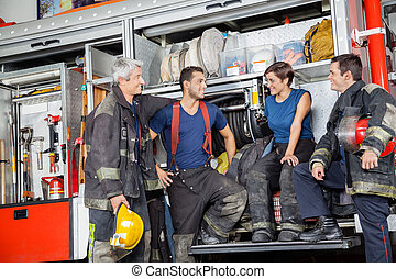Firefighters Communicating By Firetruck At Station - Team of...