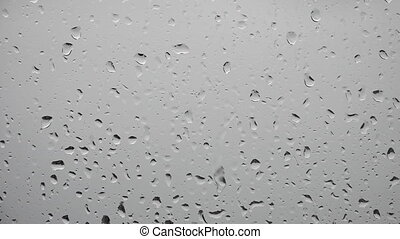 Rain drops falls on a window on a stormy day abstract...