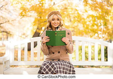 A woman relaxing in an autumn park - Beautiful smiling young...