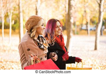 Women relaxing in an autumn park - Two girls having a...