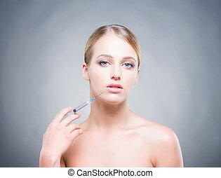 Young woman with syringe injecting botox into smooth skin