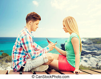 couple with smartphones sitting on bench - summer, vacation,...