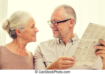 happy senior couple reading newspaper at home - family,...