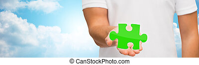 man holding green puzzle over sky background