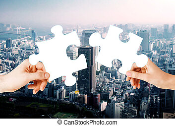 hands with green puzzle over city background - nature,...