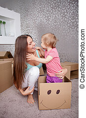 Cute family is packing things for moving - Pretty mother and...