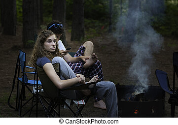 teen girl by a campfire - teenage girl sitting by a...