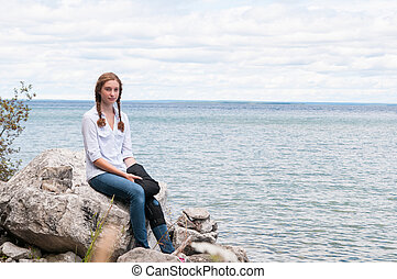 teen girl sitting by a lake