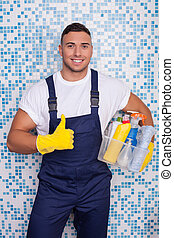 Handsome young male janitor is cleaning the house -...