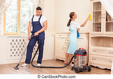 Cheerful young workers are cleaning the house with joy -...