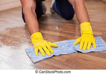 Skilled young cleaner is mopping floor in a house - Close up...