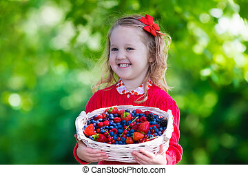 Little girl with fresh berries in a basket - Child picking...