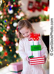 Little girl opening presents on Christmas morning - Family...