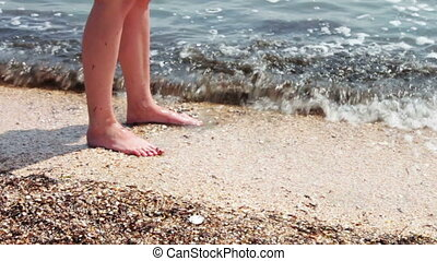 Legs of a beautiful girl on a sandy beach washed by the sea waves of the sea.