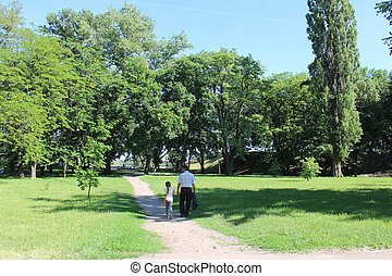 father with his daughter have a rest in park with big trees