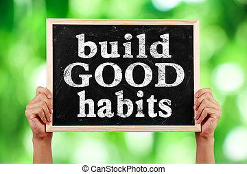 Build Good Habits - Hands holding blackboard with text Build...