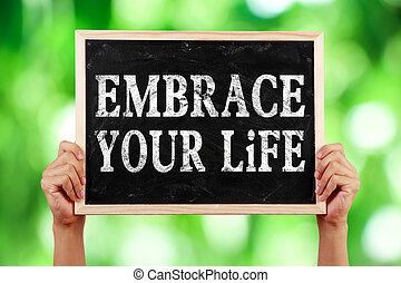 Embrace Your Life - Hands holding blackboard with text...