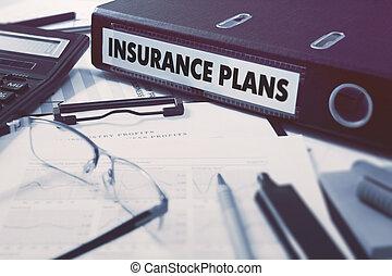 Insurance Plans on Ring Binder Blured, Toned Image -...