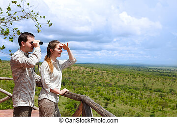 Safari vacation - Young couple in safari clothes observing...